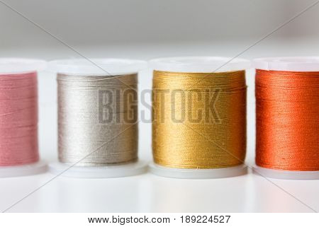 needlework, craft, sewing and tailoring concept - row of colorful thread spools on table