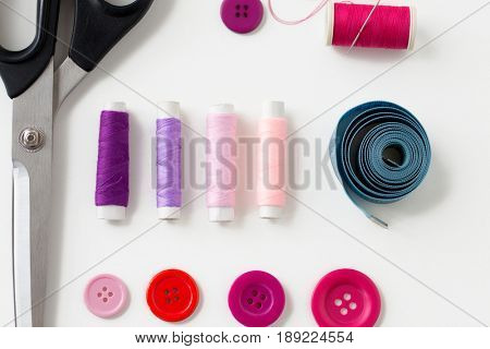 needlework and tailoring concept - scissors, sewing buttons, spools of thread and tape measure