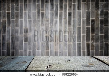 Selected focus empty gray wooden table and wall texture or old black brick wall blur background image. for your photomontage or product display.