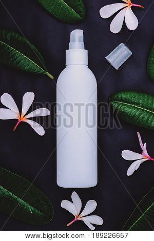 Cosmetic bottle containers with green herbal leaves Blank label for branding mock-up Natural beauty product concept.Vintage tone