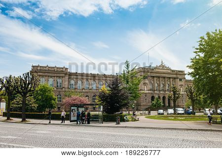 STRASBOURG FRANCE - MAY 18 2016: people waiting for the bus at the station with the majestic Strasbourg University main building in the background