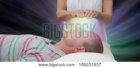 Channelling Healing Energy - female with hands held six inches above a male patient's face displaying coloured light on a dark background