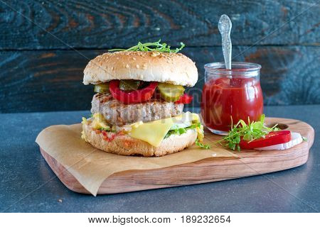 Homemade burger with bread, cheese, tomato, lettuce, tomato sauce, pickles and onions on a wooden cutting board with jar of tomato sauce, parsley, onion and tomato slices. Home healthy eating.
