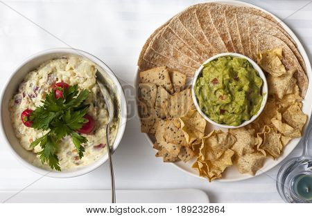 Mexican tacos nachos tortillas and guacamole. Russian salad. In a dish is potato salad with cherry tomatoes and parsley to garnish, and the other a typical Mexican dish of guacamole and tacos.