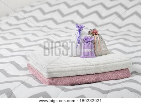 Aromatic potpourri set on bed. Three lavender scent pouches on towels. Scented sachets in bedroom. Fragrance bags for fresh home. Decoration, furnishing and storage items.