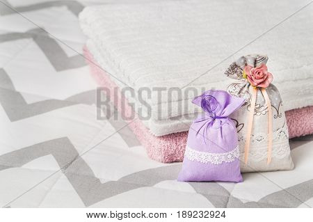 Two scented sachets leaning on two towels on bed. Fragrant lavender pouches for home interior design and storage. Decorative bags with nice smell. Aromatic potpourri. Decoration accessories.