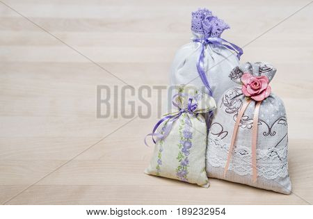 Three lavender scent pouches on wooden board or table. Scented sachets on wood with copy space. Fragrance bags for fresh home. Decoration, furnishing and storage accessories. Aromatic potpourri set.