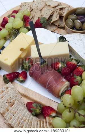 Ham, chips and crackers, olives, grapes, strawberries and cheese. A plate full of food for buffett. A fork on the ham.