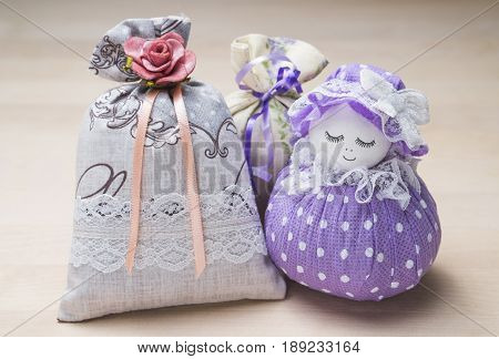 Scented sachets and pouch figure of a girl. Close up of bags filled with lavender on wooden table or board. Decoration, furnishing and storage accessories. Aromatic potpourri set on wood.