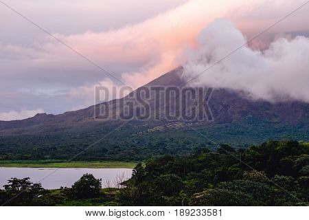 Volcano of Arenal covered in clouds at sunset. Costa Rica
