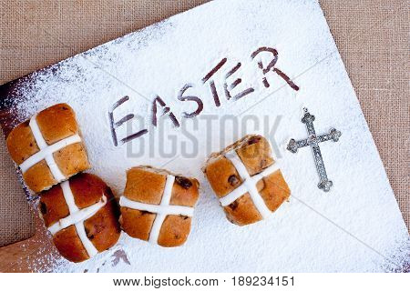 Easter - Hot Cross Buns on floured wooden cutting board, with word Easter written in flour - with silver cross