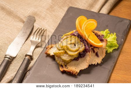 Danish specialties and national dishes high-quality open sandwich. Roasted Pork belly and Pickled red cabbage and orange served on a plate and ready for eating