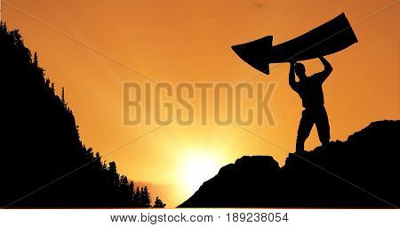 Digital composite of Silhouette businessman holding arrow sign against sky during sunset