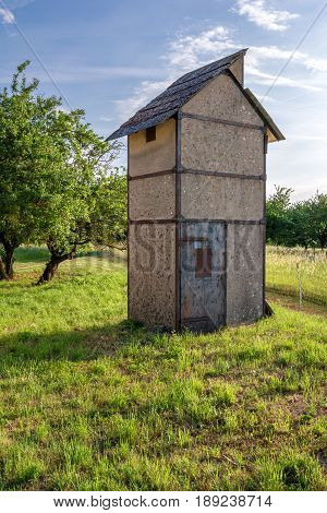 French countryside. A small old stone tower in a garden landscape.
