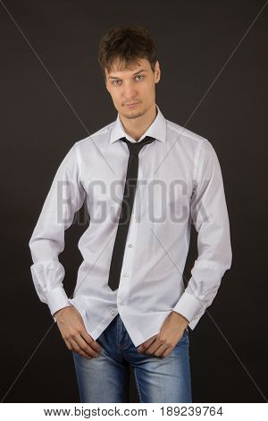 Sexy stylish young man in a white shirt with a black tie and expensive cufflinks on the black background
