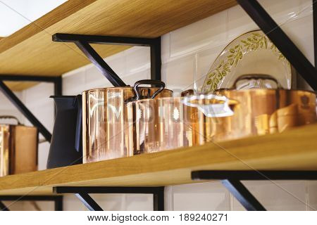 Beautiful kitchen utensils on a wooden shelf. Classical copper cookware for cooking, copper pots and buckets. Soft focus and beautiful bokeh.