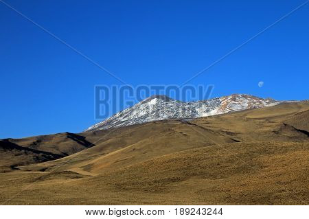 Snowcovered Volcano Tromen with full moon, Patagonia, Argentina