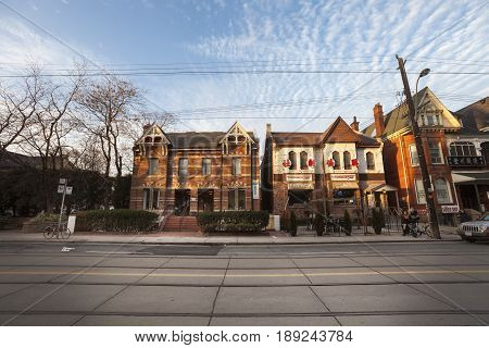 TORONTO, CANADA. December 26, 2014: Chinatown in Toronto, Canada. Urban street in the city center. Houses and dwellings in line with activities and shops. Front photo. Blue sky with some clouds.