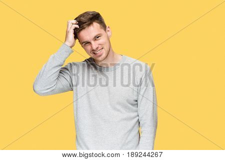 The young man smiling and looking at camera on yellow studio background