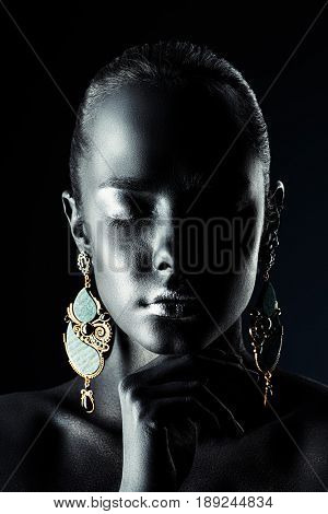 Close-up portrait of a gorgeous young woman with perfect black skin and silver glitter lips wearing beautiful earrings. Body painting project. Cosmetics and make-up. Jewelry and bijouterie.