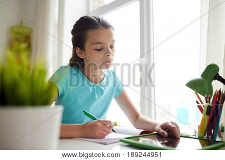 people, children, education and learning concept - girl with tablet pc computer doing homework and writing to notebook at home