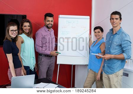 Portrait of smiling business executives discussing over flip chart during meeting in office