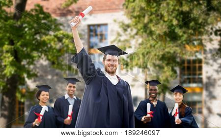 education, graduation and people concept - group of happy international students in mortar boards and bachelor gowns with diplomas over campus building background