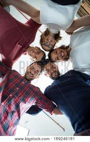 Team of businesspeople forming huddle in office
