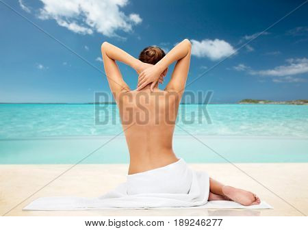 beauty, people and bodycare concept - beautiful young woman in white towel with bare top tropical beach background