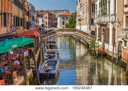 VENICE, ITALY - MAY 23, 2017: San Lorenzo channel with bridge and pizzeria on sunny day