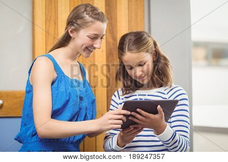 Students using digital tablet in classroom at school