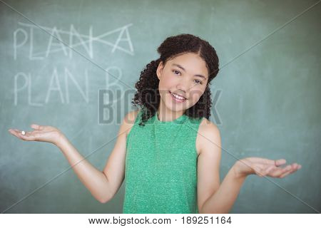 Portrait of schoolgirl gesturing while pretending to be a teacher in classroom at school