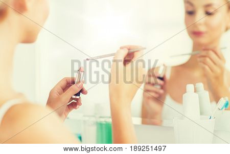 beauty, make up, cosmetics, morning and people concept - close up of young woman with lipstick and make up brush at home bathroom mirror