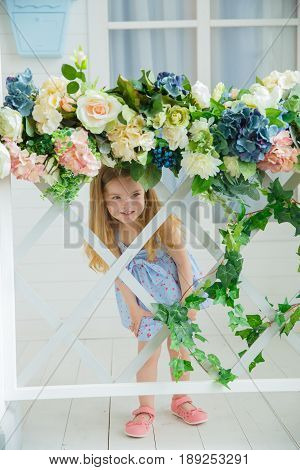 A little girl in a blue dress slyly smiles looking through the lattice of a wooden fence entwined with ivy
