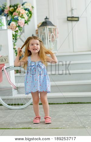 A little girl in a blue dress came down from the porch of her house and touched her hair looking enthusiastically into the distance
