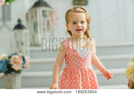 Little girl in a pink dress with enthusiasm and hope looks into the distance