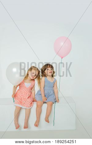 Two girls are waiting on a white box holding balloons in their hands