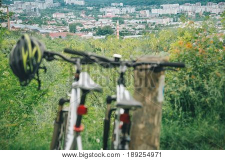 two bicycles stand on hill wth city view on background