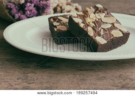 Piece of homemade dark chocolate brownies topping with almonds slices on white plate. Chocolate brownies put on wood table. Fudge brownies is one type of chocolate cake. Square shape of chocolate brownies in vintage tone for background.