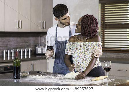 happy mixed race couple kneading dough kitchen wine, bonding together fun baking