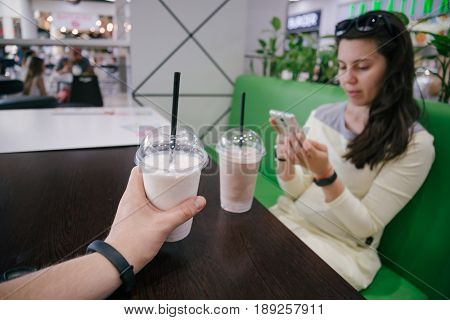 First person view look at woman that searfing on the phone in cafe with smoothie on the table