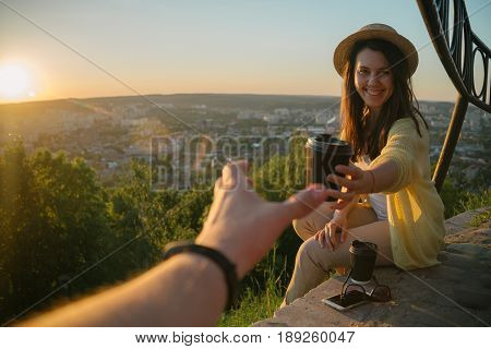Female giving coffee to man while they sitting on the hill on sunrise city on background