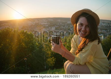 woman sit on the hill and lookin on sunset near city