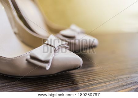 Women's beige lacquered shoes with a bow and a pointed nose with a high heel on a dark wooden background