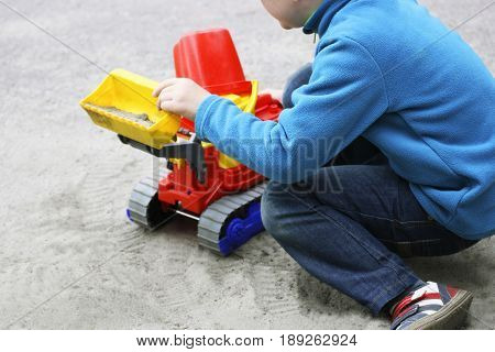 Children play in the fresh air. The image of a small child who sits and plays with large toy car on the sand .