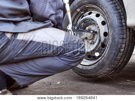 Mechanic screws the wheel to the car using cross wheel wrench