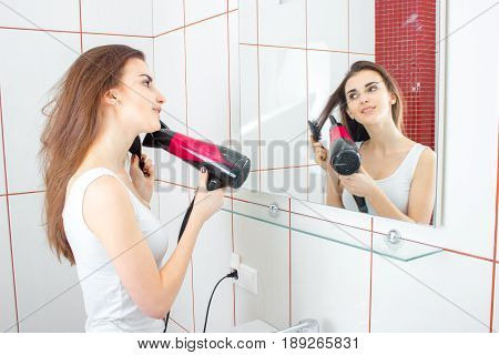 young girl with dark hair is standing in the bathroom front of the mirror and dries hair closeup