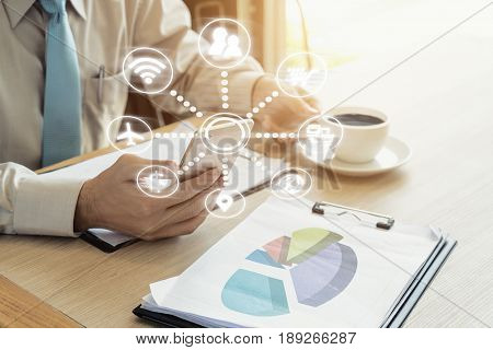 Businessman with a cup of coffee reading his smart phone in a cafe. Online communication network digital 4.0 technology internet wireless application mobile smartphone