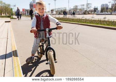 Photo of boy on run bicycle at road in park