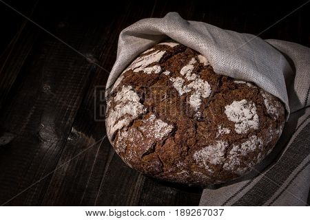 Traditional Whole Grain Rye Bread on Dark Wooden Table Background